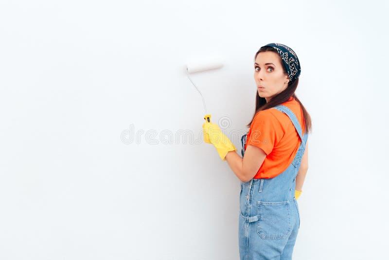 Vrouw die witte muur met verfrol schilderen stock foto's