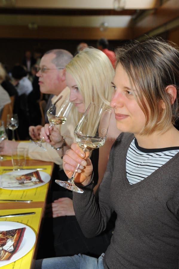 Vrouw die witte wijn proeft stock foto's