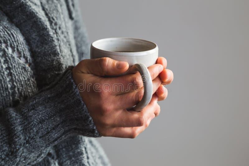 Vrouw die in wollige grijze sweater warme kop thee houden stock fotografie