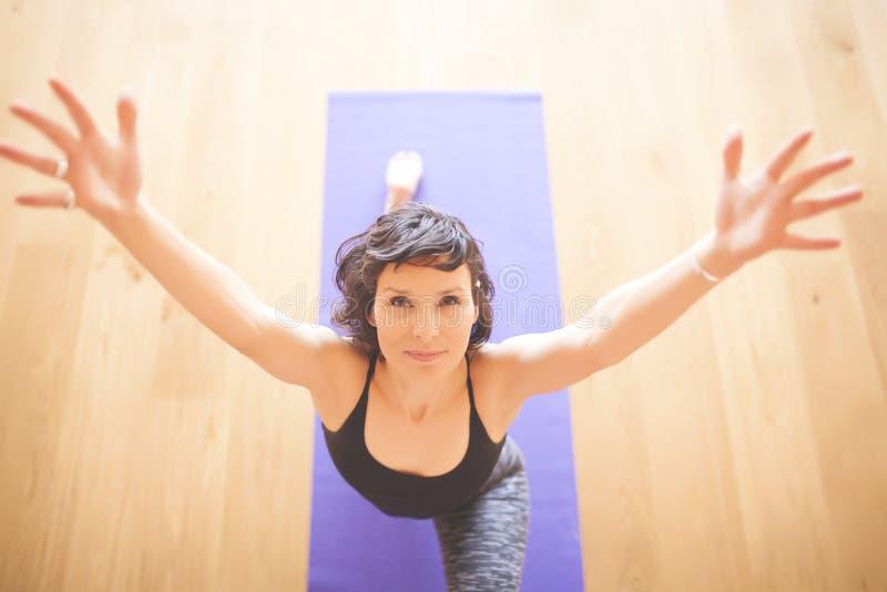 Vrouw die yoga doen bij houten vloer royalty-vrije stock foto's