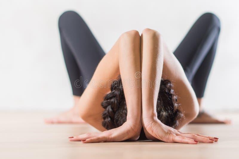 Vrouw die yoga doen die op vloer in artistieke esthetische houding liggen stock afbeeldingen