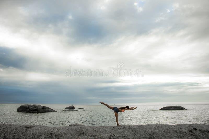 Vrouw die yoga op een rots doen bij zonsondergang op Bakovern-Strand, Cape Town royalty-vrije stock fotografie