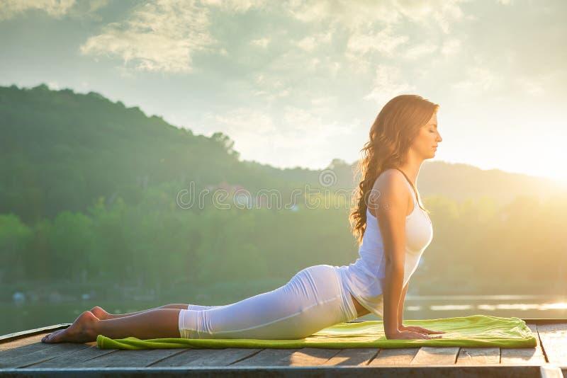 Vrouw die yoga op het meer doen stock fotografie