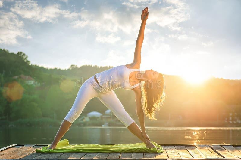 Vrouw die yoga op het meer doen stock afbeeldingen