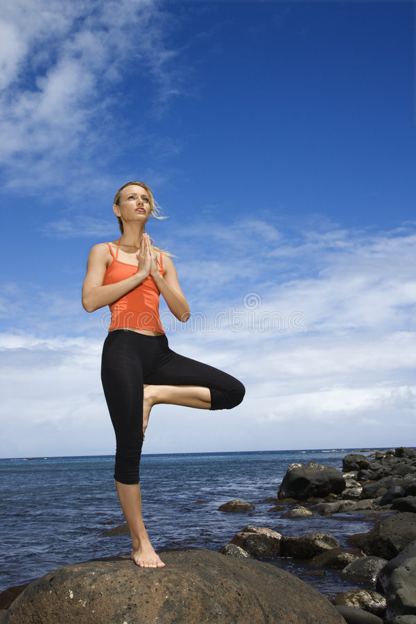 Vrouw die yoga op rotsachtige kust doet. stock afbeeldingen