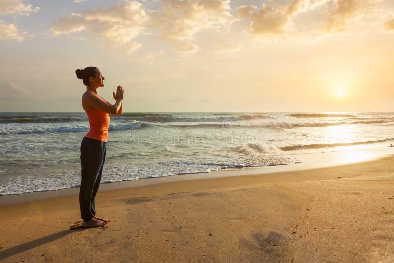 Vrouw die yoga op strand doet stock foto