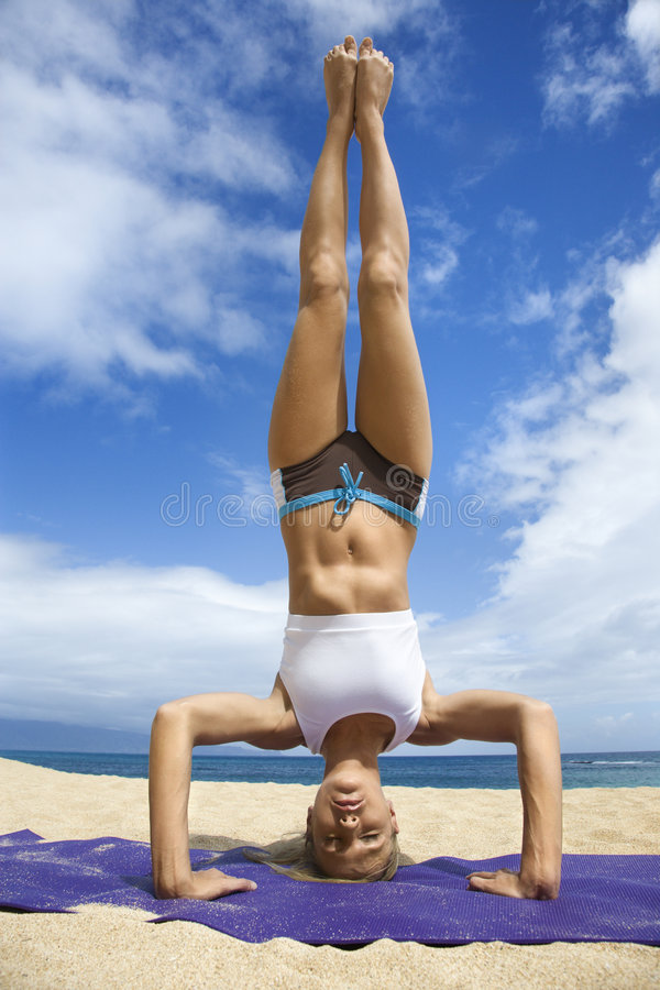 Vrouw die yoga op strand doet. stock afbeelding