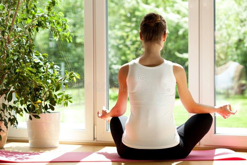 Vrouw die yoga thuis doet stock foto's