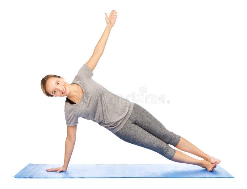 Vrouw die yoga in zijplank maakt op mat stellen stock afbeeldingen