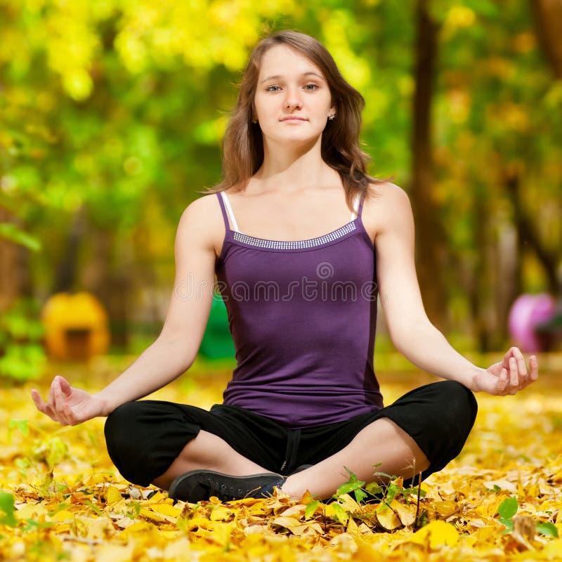 Vrouw die yogaoefeningen in het de herfstpark doen royalty-vrije stock foto's