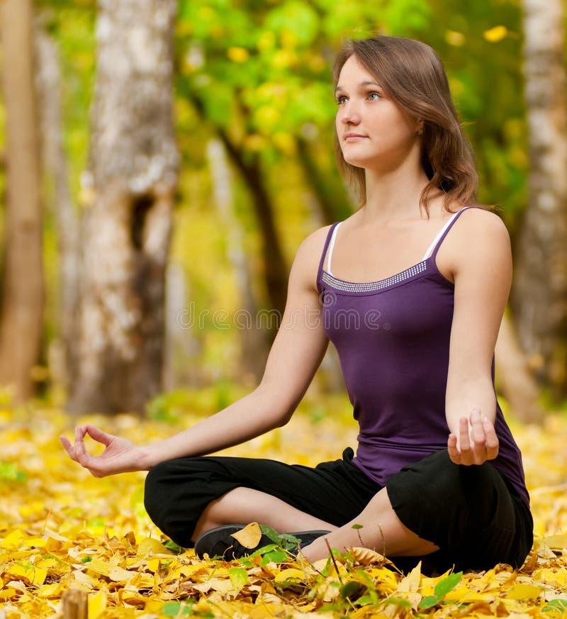 Vrouw die yogaoefeningen in het de herfstpark doet stock afbeelding