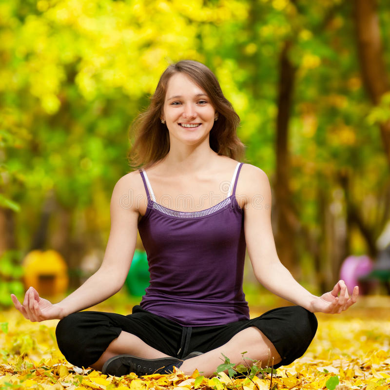 Vrouw die yogaoefeningen in het de herfstpark doet royalty-vrije stock foto's