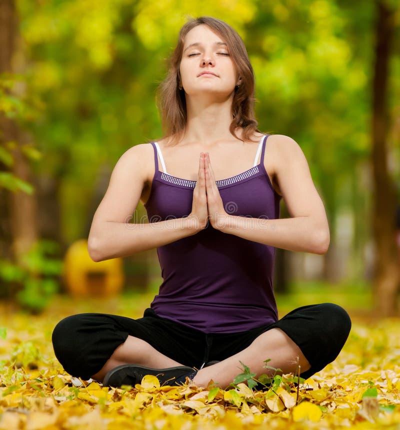 Vrouw die yogaoefeningen in het de herfstpark doet royalty-vrije stock foto