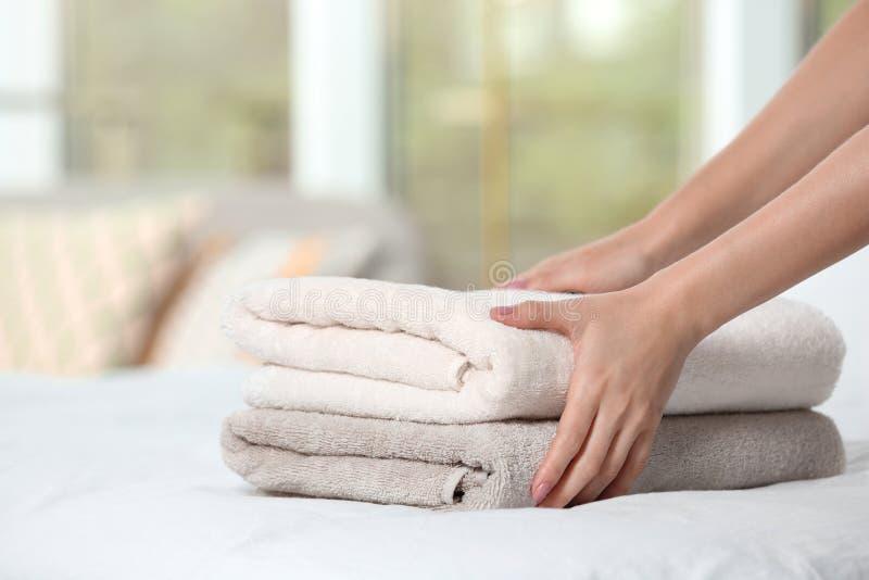 Vrouw die zachte schone badstofhanddoeken op bed zetten stock foto's