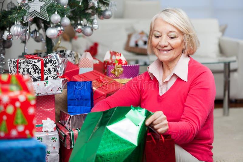 Vrouw die in Zak kijken terwijl het Zitten door Kerstmis royalty-vrije stock afbeeldingen