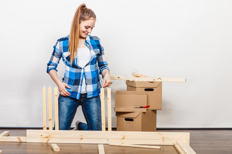 Vrouw die zich in assemblagemeubilair bij nieuw huis bewegen royalty-vrije stock afbeeldingen