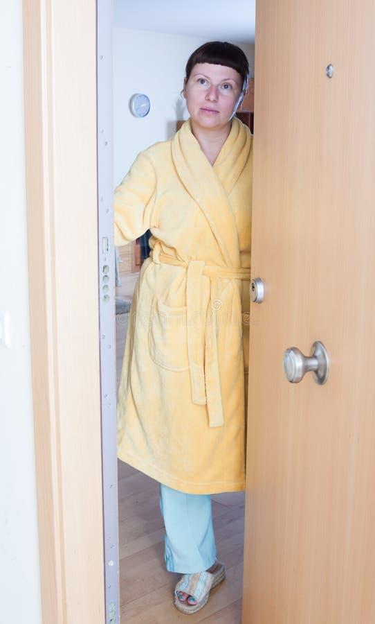 Vrouw die zich bij de deur bevinden stock fotografie
