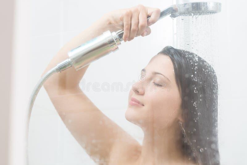 Vrouw die zich bij de douche bevinden royalty-vrije stock afbeelding