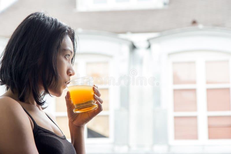 Vrouw die zich bij een open venster bevinden royalty-vrije stock fotografie