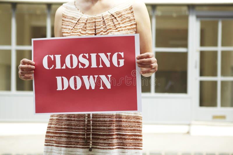 Vrouw die zich buiten Lege Winkelholding bevinden die Teken sluiten stock fotografie