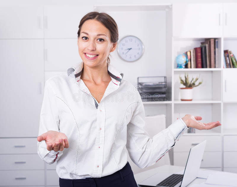 Vrouw die zich in bureau bevinden stock afbeelding