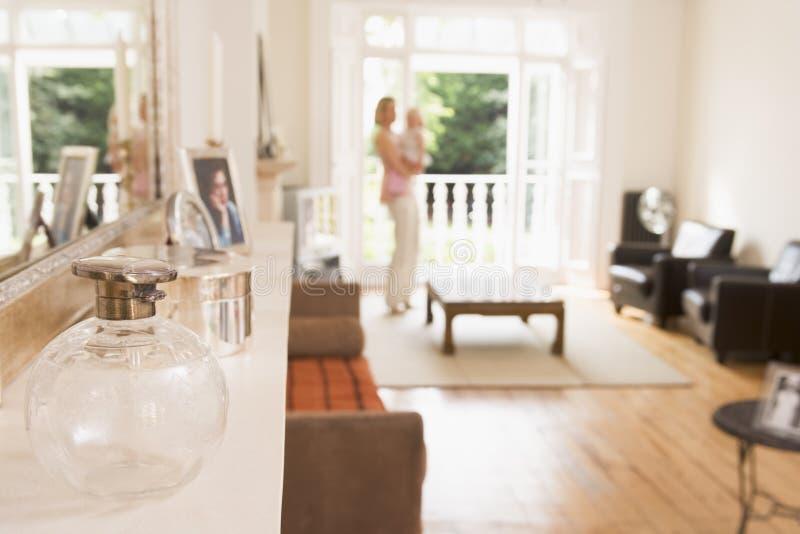 Vrouw die zich in de baby van de woonkamerholding bevindt royalty-vrije stock foto