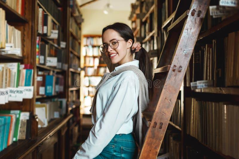 Vrouw die zich dichtbij Boekenrekken bevinden royalty-vrije stock afbeelding
