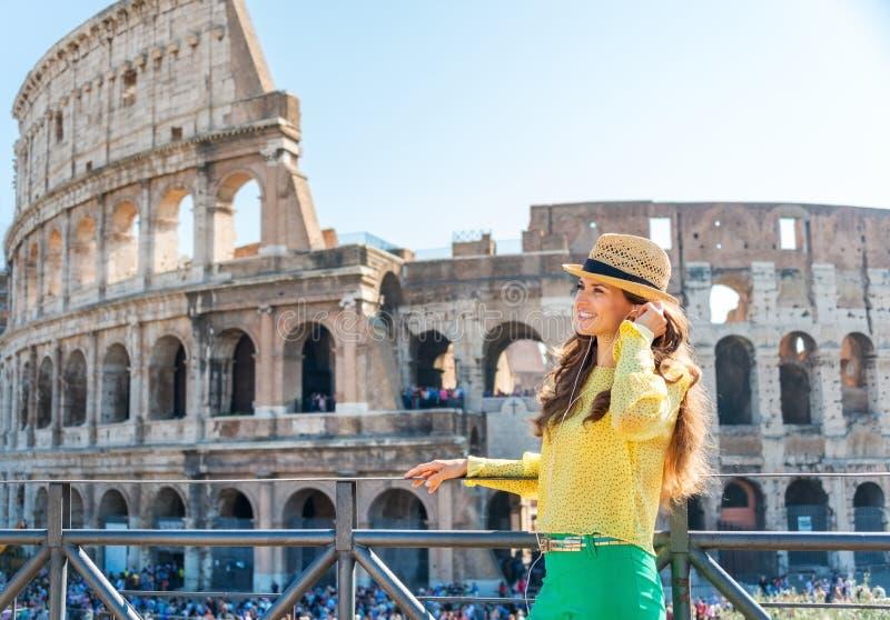 Vrouw die zich dichtbij Colosseum in Rome bevinden die aan muziek luisteren royalty-vrije stock foto's