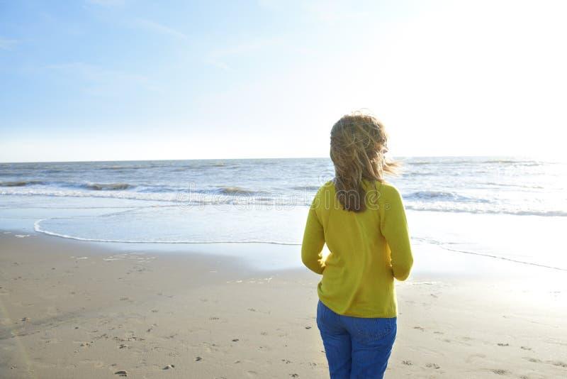 Vrouw die zich eenzaam op het strand en het overzees bekijken bevinden stock foto's