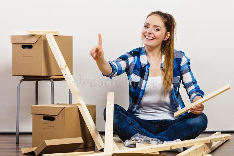 Vrouw die zich in het meubilair van de flatassemblage bewegen stock fotografie