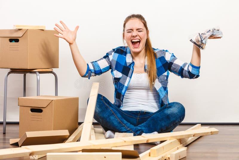 Vrouw die zich in holdingsschroeven en meubilairdelen bewegen royalty-vrije stock fotografie