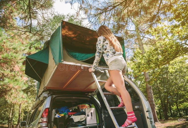Vrouw die zich in ladder het openen tent over auto bevinden royalty-vrije stock afbeelding