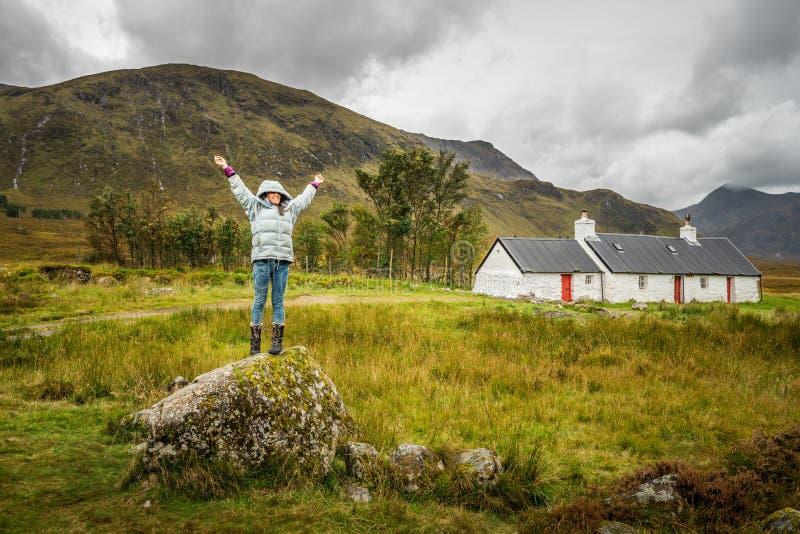 Vrouw die zich met open wapens tegen achtergrond van berg bevinden royalty-vrije stock fotografie