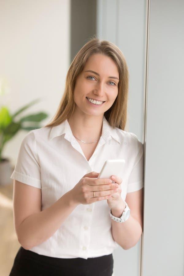 Vrouw die zich met in smartphone in handen bevinden royalty-vrije stock afbeelding