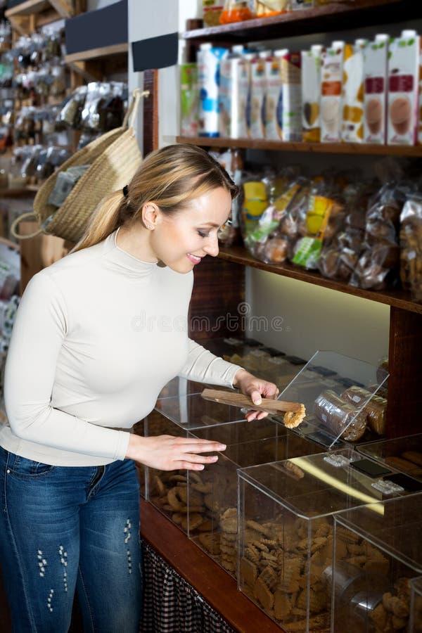 Vrouw die zich naast containers met droge koekjes bevinden stock foto's