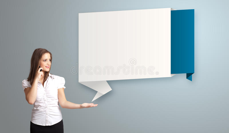 vrouw die zich naast de moderne ruimte van het origamiexemplaar bevinden en telefoongesprek maken stock afbeeldingen