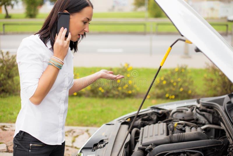 Vrouw die zich naast gebroken auto bevinden en op telefoon spreken royalty-vrije stock afbeeldingen