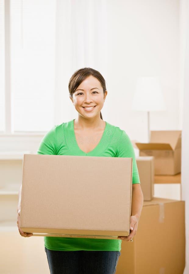 Vrouw die zich in nieuw huis beweegt stock foto's
