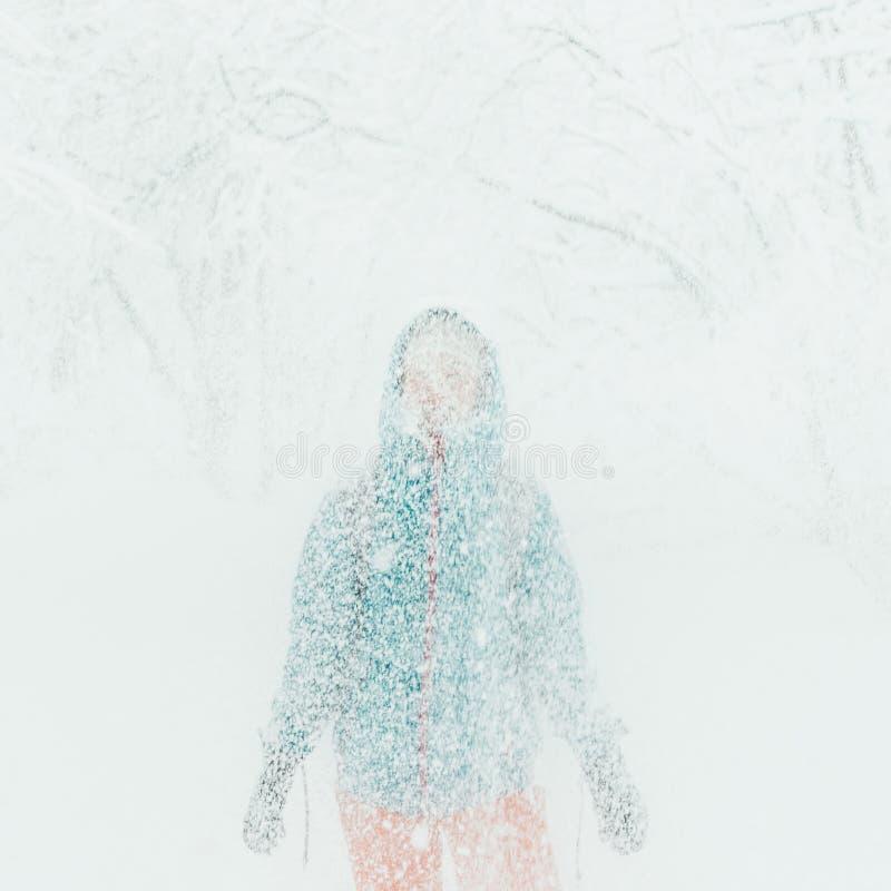 Vrouw die zich onder dalende sneeuw bevinden royalty-vrije stock foto's