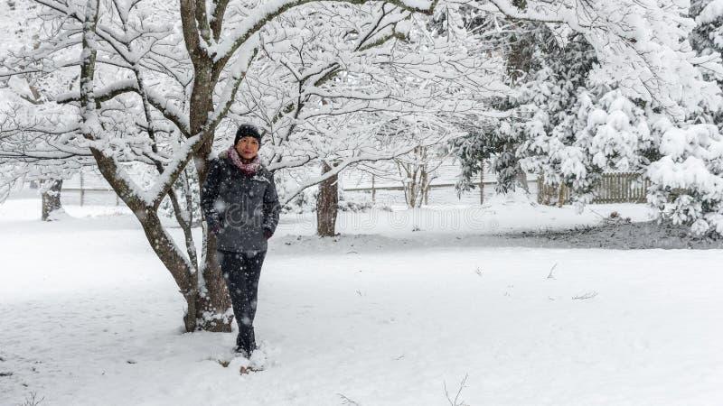 Vrouw die zich onder sneeuw behandelde boom bevinden royalty-vrije stock afbeeldingen