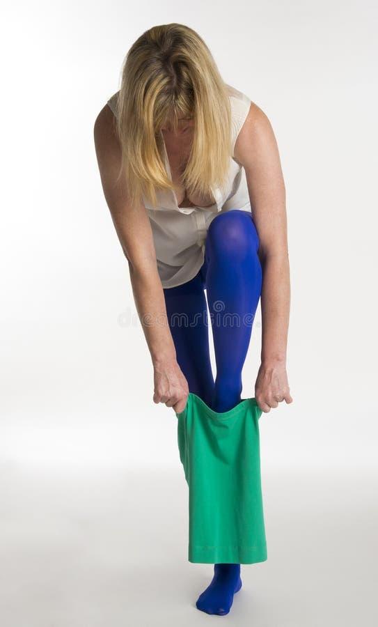 Vrouw die zich op één been bevinden die gekleed worden stock foto