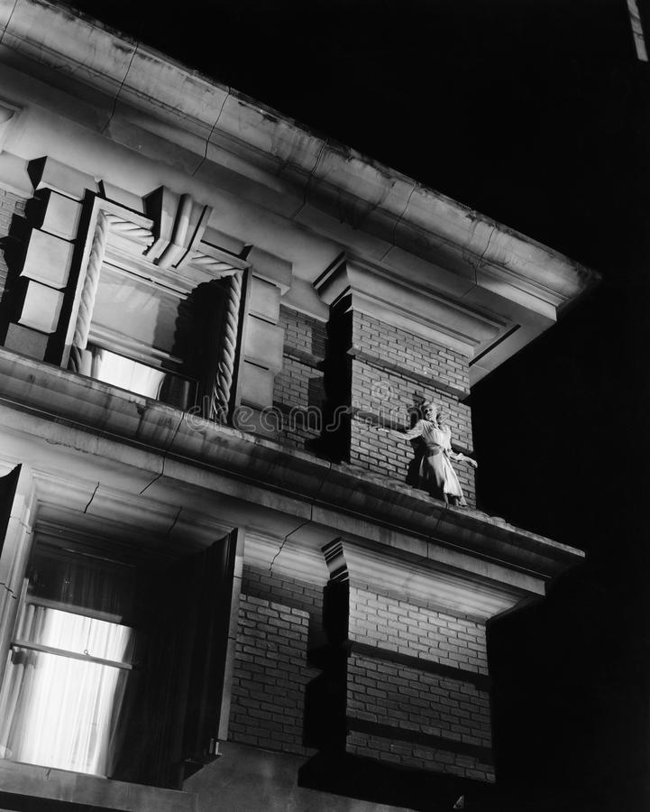 Vrouw die zich op de bovenkant van een gebouw op een richel bevinden (Alle afgeschilderde personen leven niet langer en geen land royalty-vrije stock fotografie
