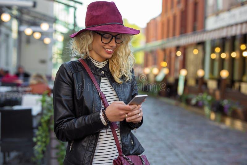 Vrouw die zich op de straat en het texting bevinden royalty-vrije stock foto's