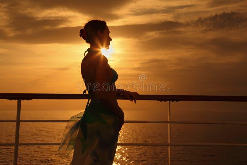 Vrouw die zich op dek van cruiseschip bevindt stock afbeelding