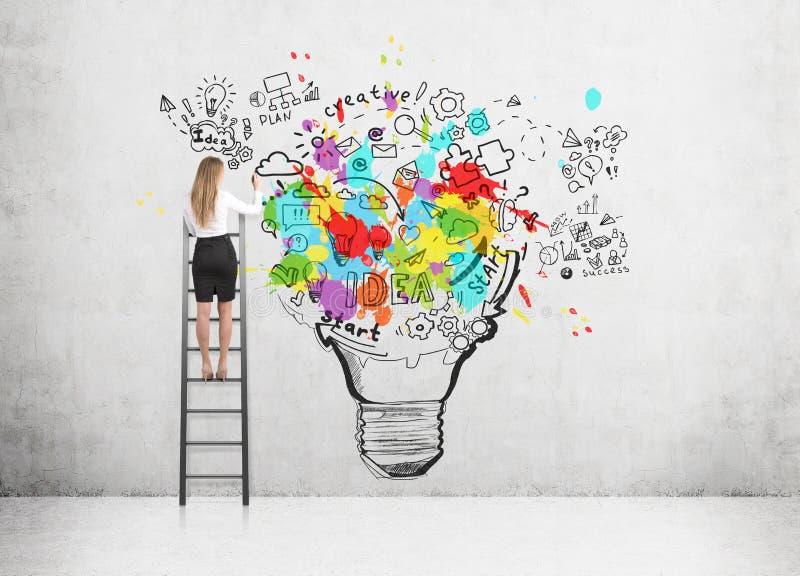 Vrouw die zich op een ladder bevinden en een grote en kleurrijke gloeilampenschets trekken op een concrete muur stock afbeeldingen