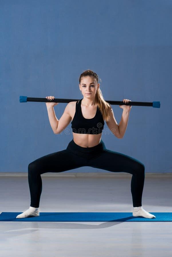 Vrouw die zich op een mat bevinden, die een geschiktheidsstok houden stock afbeelding