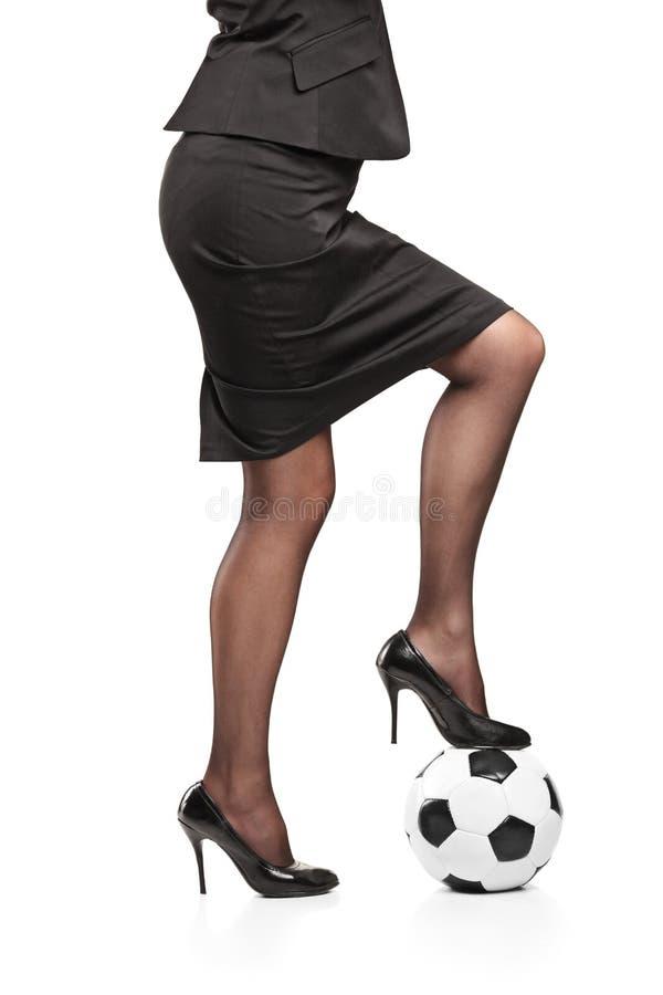 Vrouw die zich op een voetbalbal bevindt stock foto