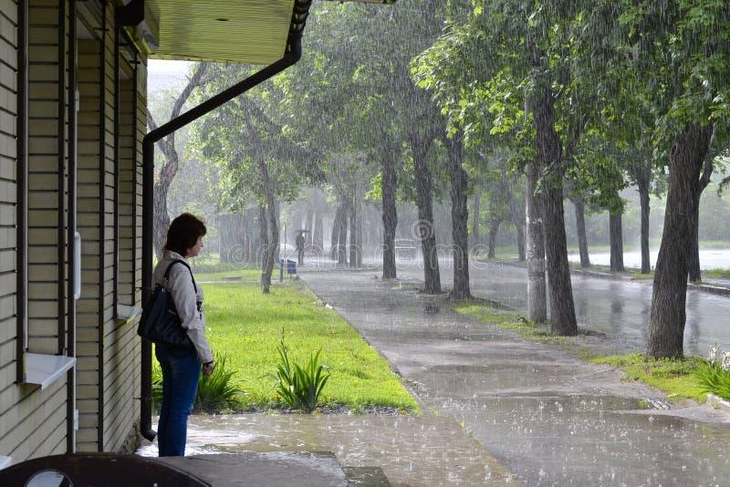 Vrouw die zich op een winkelsportiek bevinden en terwijl regenend eind wachten stock fotografie