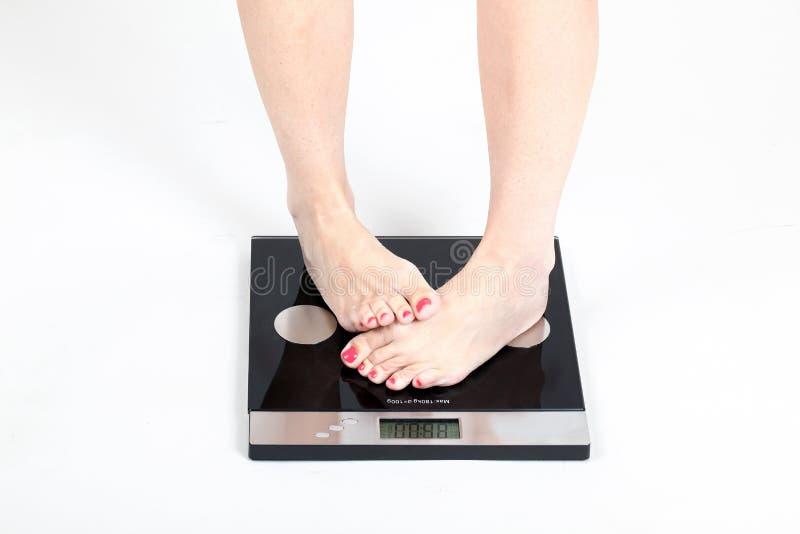 Vrouw die zich op gewichtsschalen bevinden stock afbeelding