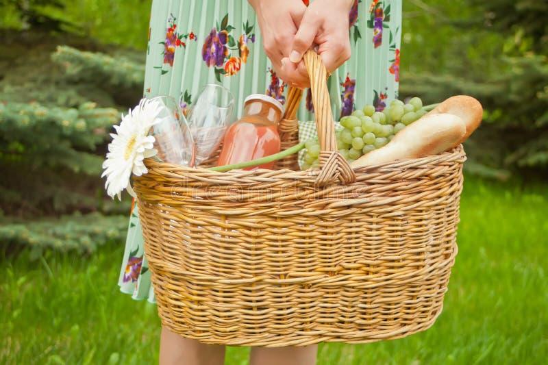 Vrouw die zich op het groene gras bevinden en picknickmand met voedsel, dranken en bloem houden stock fotografie